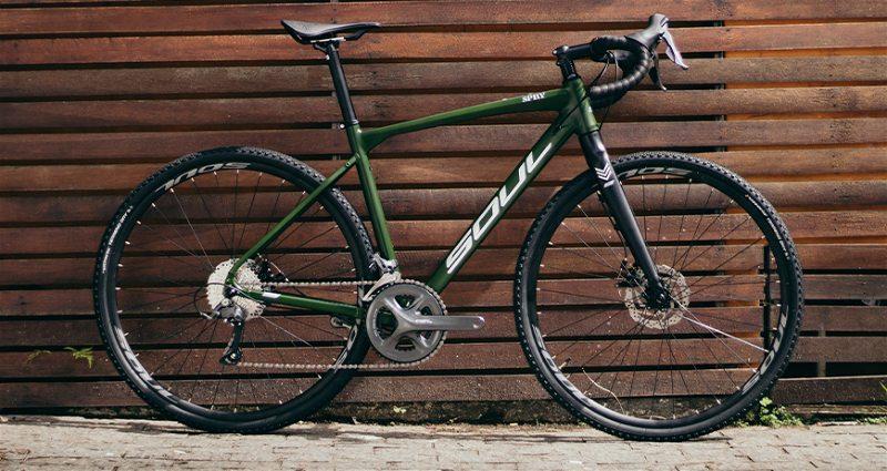 Bicicleta Gravel Soul encosta em parede de madeira