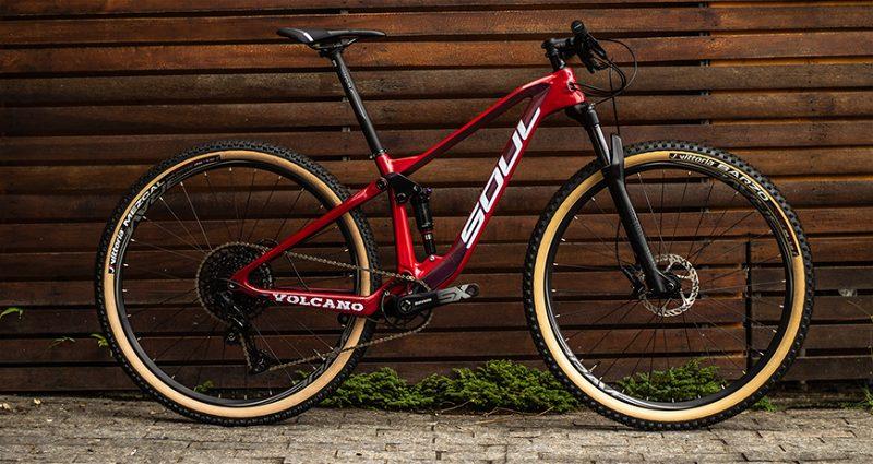 Bicicleta Mountain Bike na cor vermelha encostada em parede de madeira