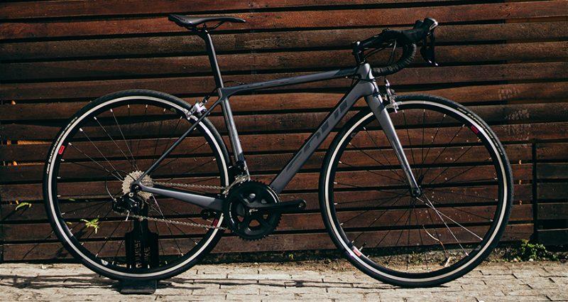 Bicicleta Road Soul encostada em parede de madeira