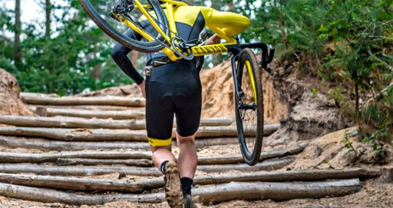 Ciclista com roupas adequadas para a prática do esporte carregando sua bicicleta nas costas em uma escada feita de madeira em local da natureza