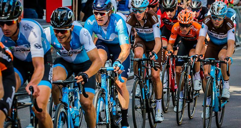 Ciclistas em suas bicicletas um atrás do outro em prova de competição