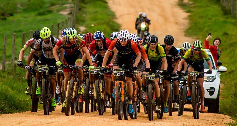 Montante de ciclistas andando de bicicleta em estrada de terra