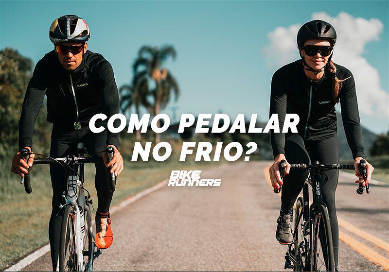 Dois ciclistas, homem e mulher, andando de bicicleta em estrada com roupas de frio