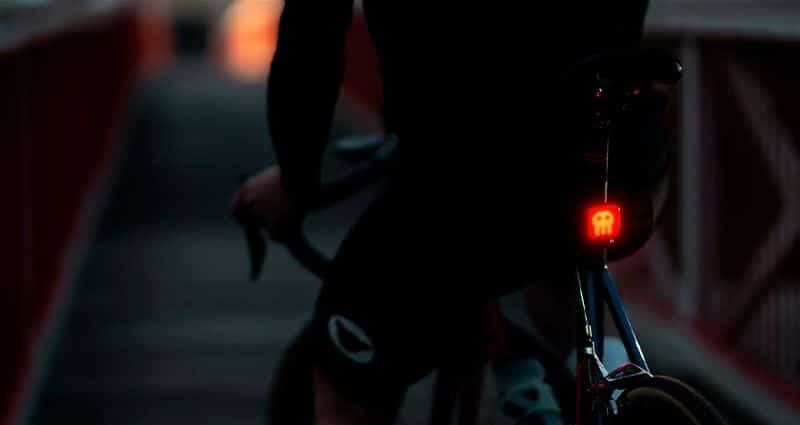 Imagem escura de pessoa sentada em bicicleta virada de costas e iluminação traseira da bicicleta