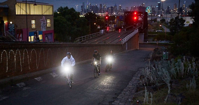 Três pessoas andando de bicicleta com iluminação em rua escura