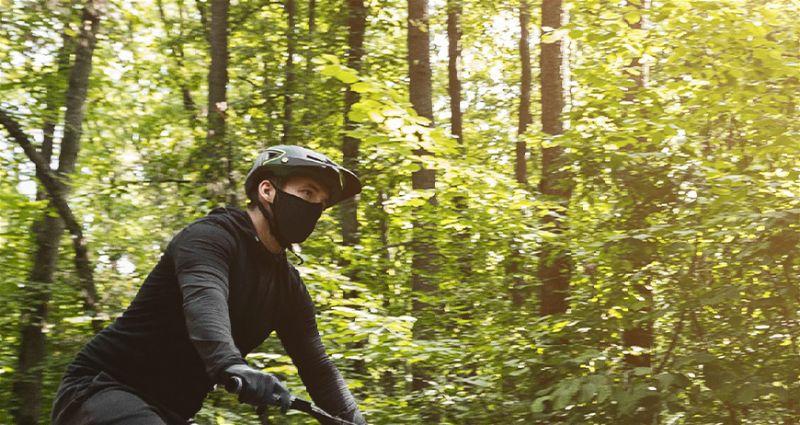 Pessoa pedalando em local cheio de árvores utilizando roupas de frio e máscara