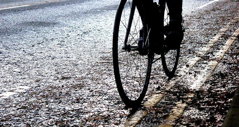 Imagem de ciclista passando em rua cheia de água da chuva