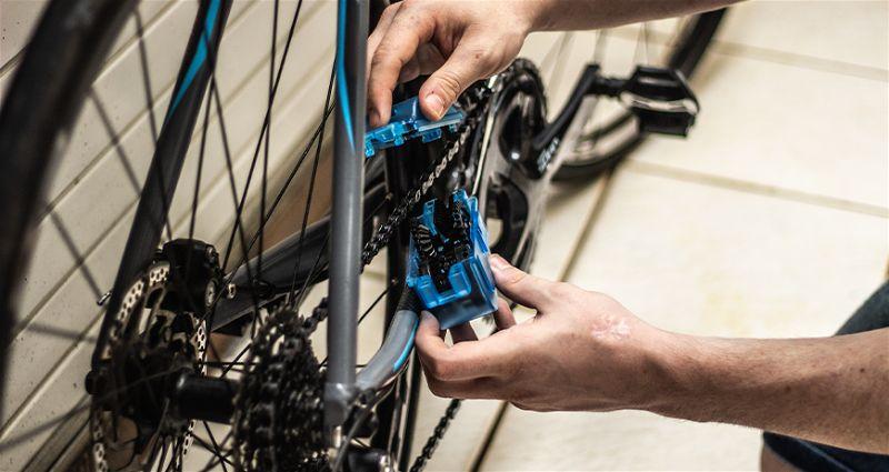 Imagem focada em parte traseira de bicicleta e mão fazenda manutenção