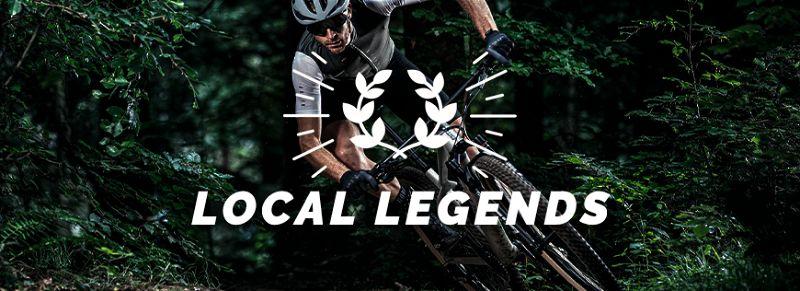 Imagem com ciclista andando rapidamente de bicicleta com roupas adequadas para a prática em local arborizado