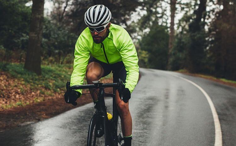 homem pedalando estrada com jaqueta corta vento
