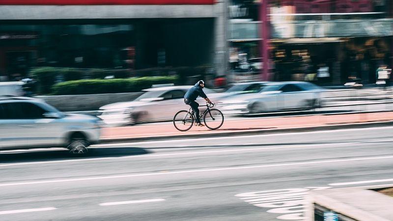 pessoa andando de bike na ciclovia no meio de carros