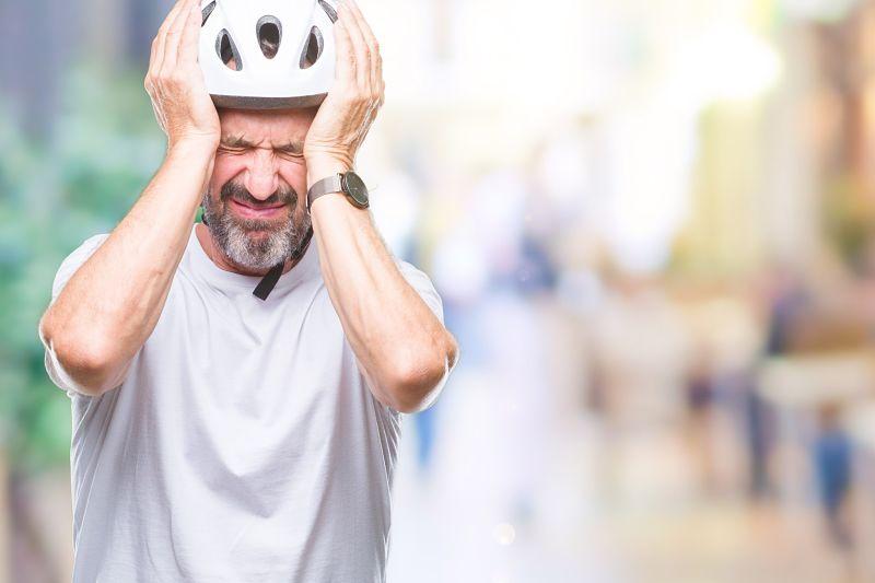 homem ciclista com dor de cabeça
