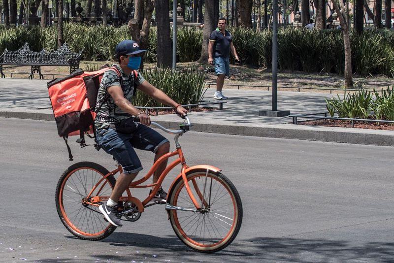 entregador de comida de bicicleta com máscara