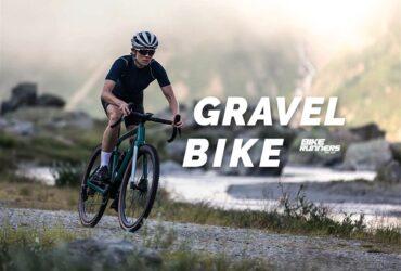 Ciclista com roupa adequada para a prática de cilcismo, andando em bicicleta em local de pedras