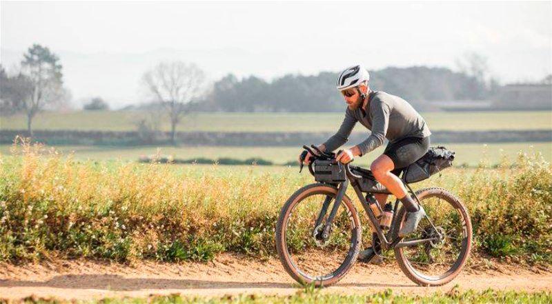 Ciclista andando em bicicleta gravel em estrada de terra