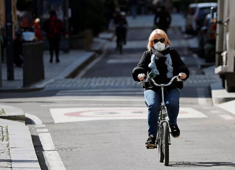 mulher andando de bicicleta com máscara