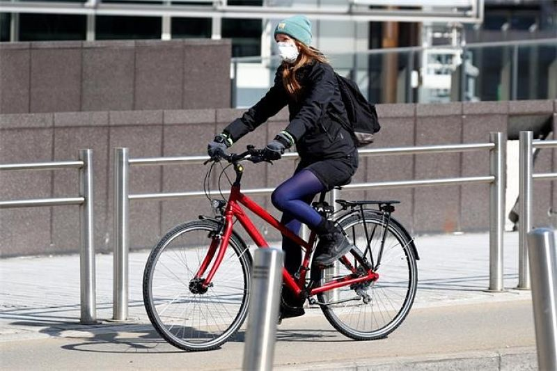 mulher andando de bike na cidade com máscara