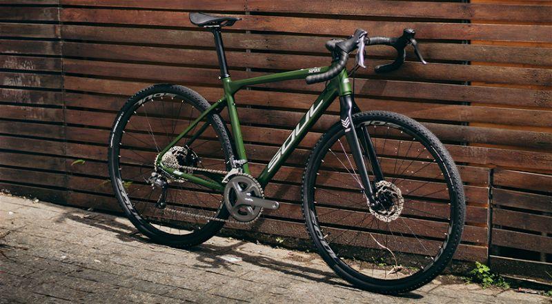 Bicicleta gravel na cor verde encostada em parede de madeira