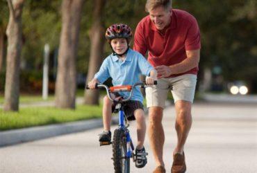 Pai ensinando criança a andar de bicicleta