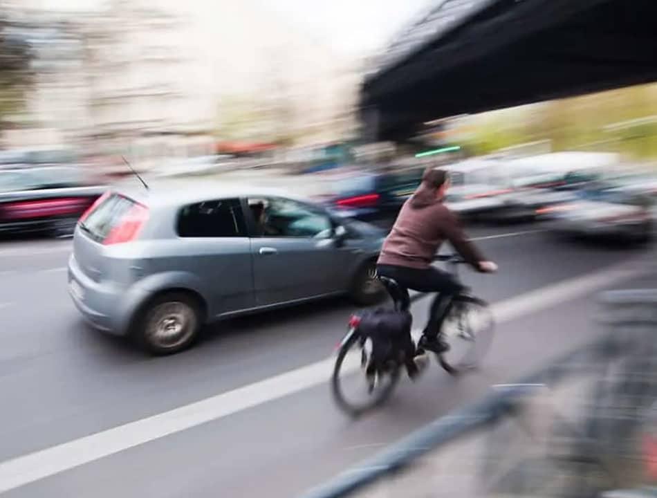 Ciclista em rua movimentada por carros andando ao lado dos carros