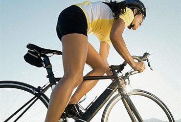 Mulher ciclista em sua bicicleta com roupas adequadas para a prático do ciclismo
