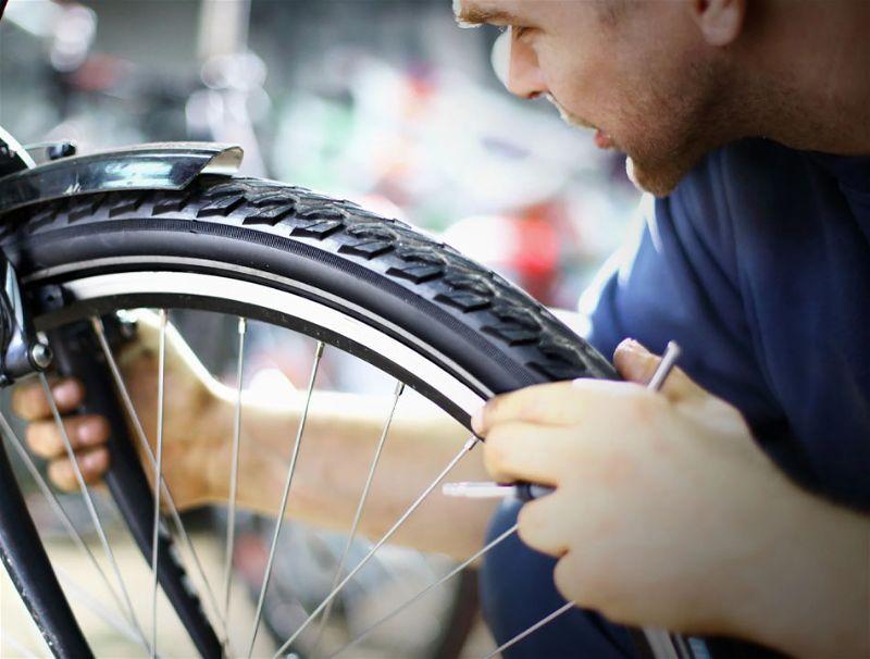 Pessoa abaixado segurando com as duas mãos pneu da bicicleta
