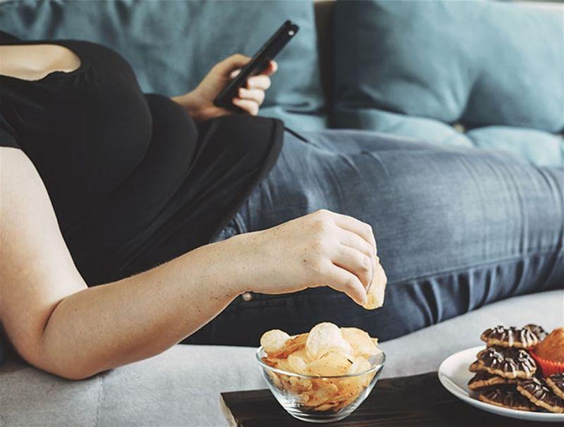 Mulher deitada em sofá segurando controle remoto e comendo aperitivos