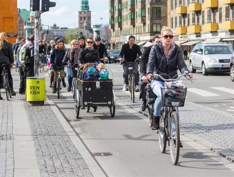Várias pessoas andando de bicicleta sobre calçada movimentada