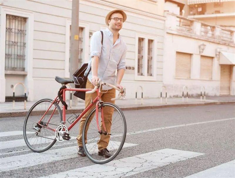 Rapaz em pé segurando bicicleta sobre faixa de pedestre