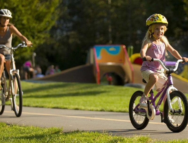 Mãe e filha andando de bicicleta em local arborizado