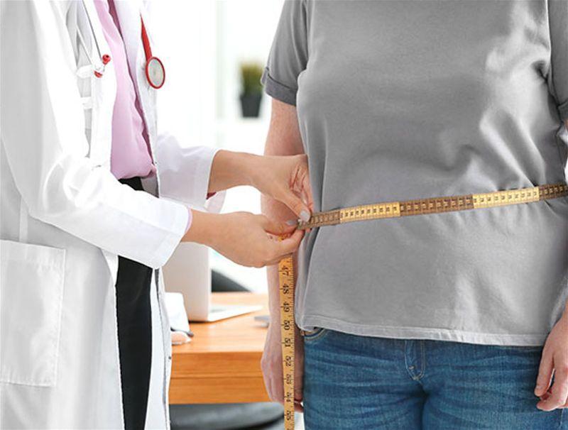 Médica medindo circunferência de barriga de paciente