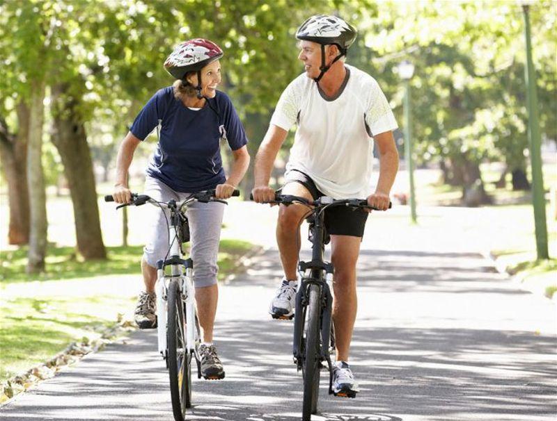Duas pessoas andando de bicicleta em um local que parece bosque