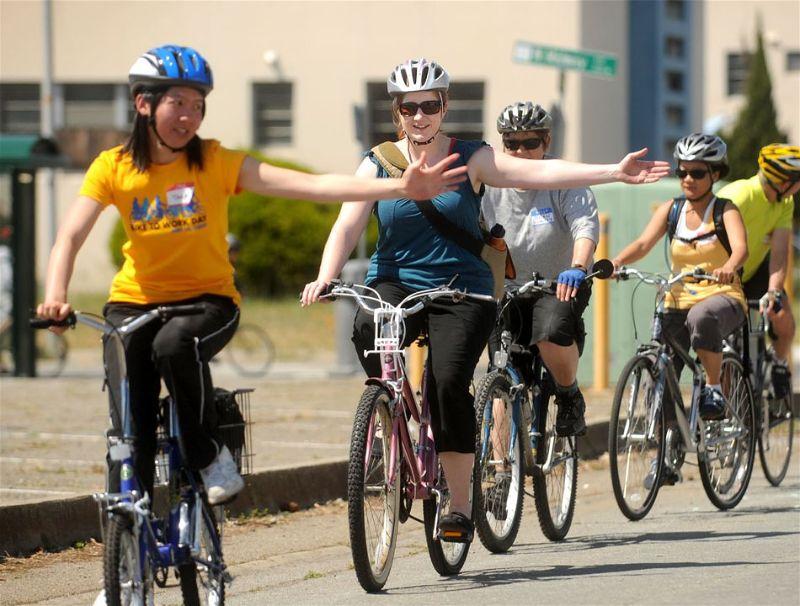 Vários ciclistas acenando com a mão indicando que vão virar para algum lado
