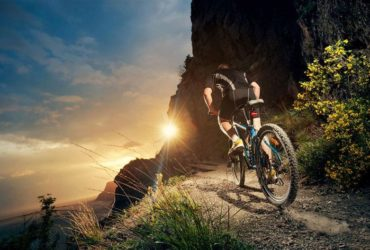Ciclista fazendo trilha ao entardecer