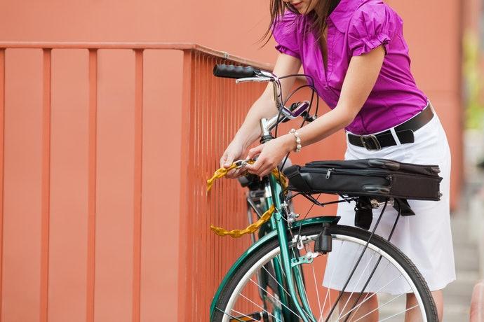 Mulher amarrando sua bicicleta em muro com cadeado de corrente