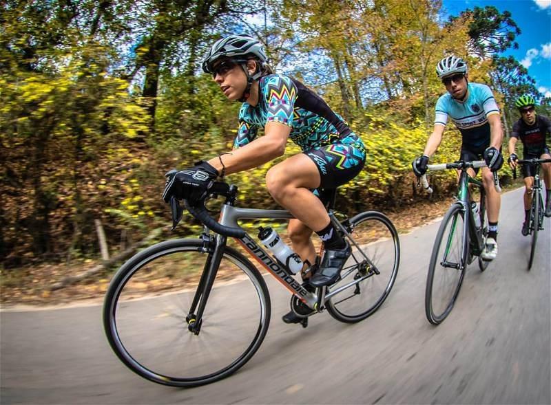 Ciclistas utilizando roupas especiais para a atividade, andando em suas bicicletas