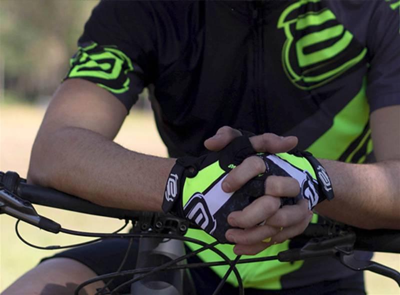 Imagem focada em mão de ciclista utilizando luvas para a prática de ciclismo
