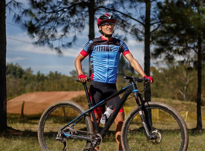 Ciclista em pé segurando bicicleta, utilizando roupas especiais para a prática da atividade de ciclismo