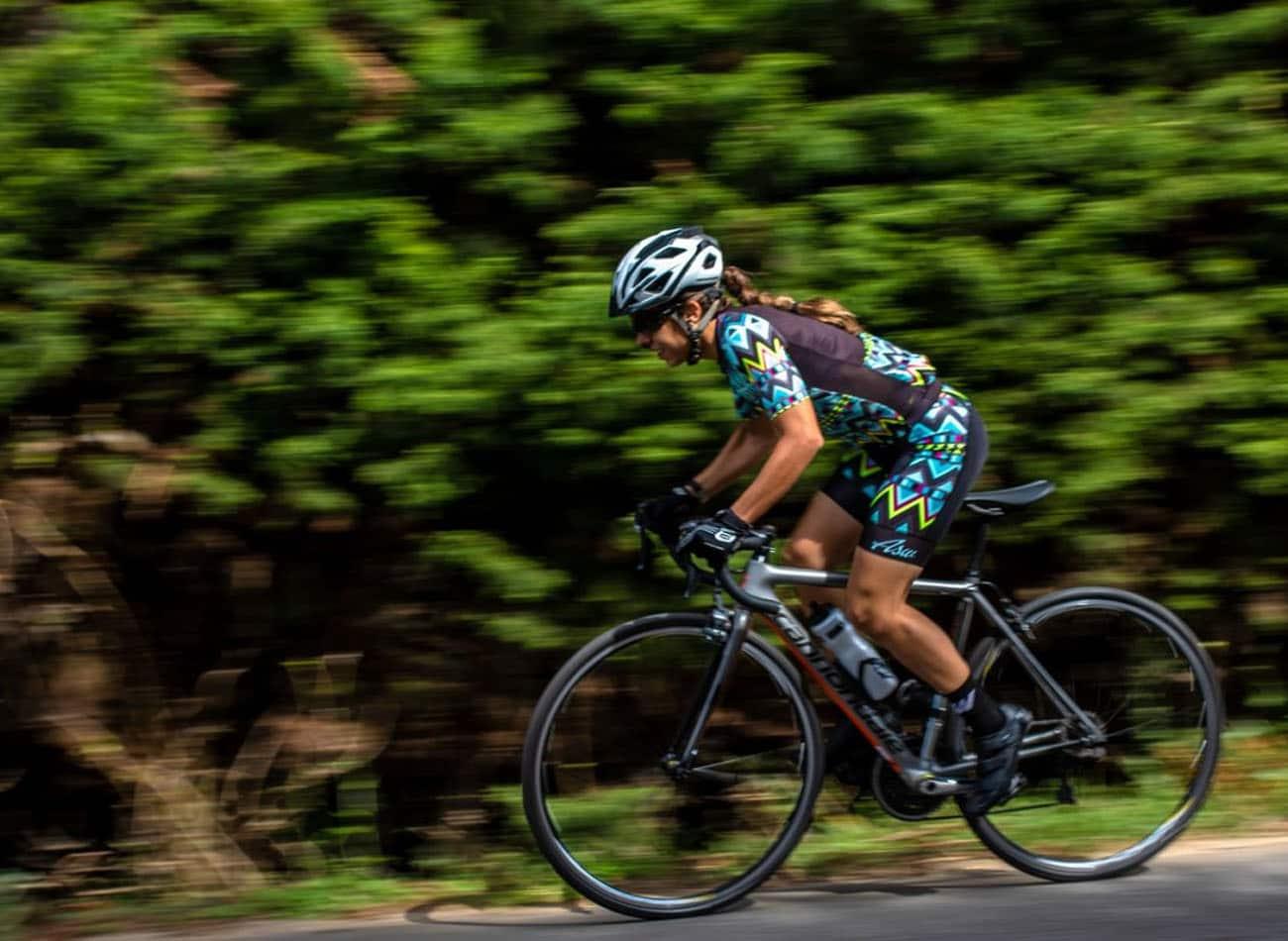 ciclista mulher pedalando na estrada em alta velocidade
