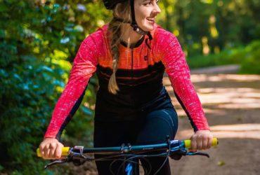 mulher pedalando sorrindo usando roupa de ciclismo rosa