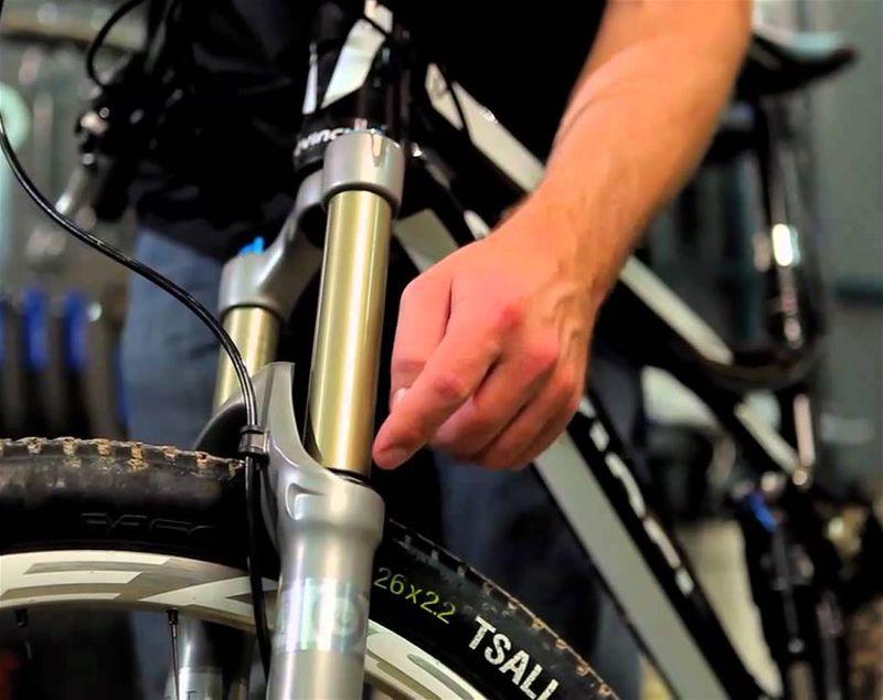 Pessoa realizando manutenção em suspensão dianteira de bicicleta