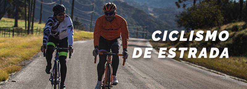 Dois ciclistas lado a lado praticando a atividade em uma estrada