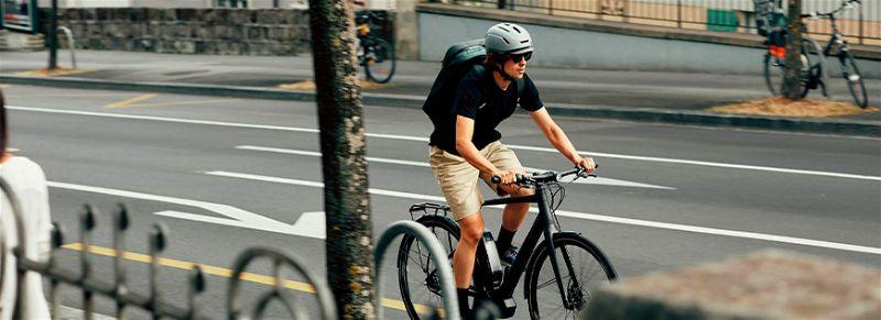Homem de capacete e mochila, andando na rua de bicicleta com bagageiro