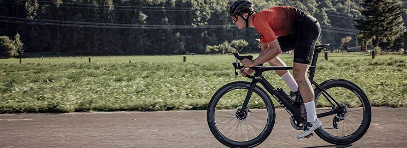 Ciclista em estrada andando de bicicleta aerodinâmica