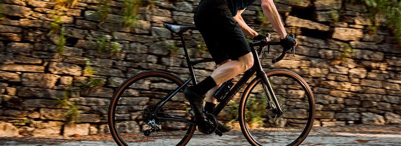 Pessoa com roupas preta andando em bicicleta própria para estrada