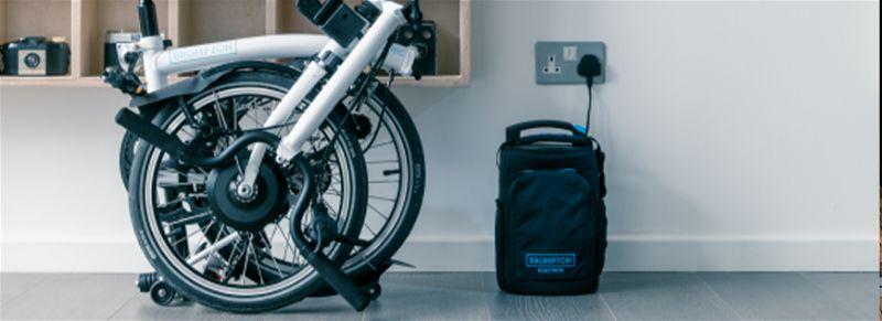 Bicicleta dobrada ao lado de uma mala apoiada no chão