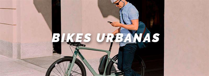 Home de capacete e mochila olhando no celular ao lado de sua bicicleta