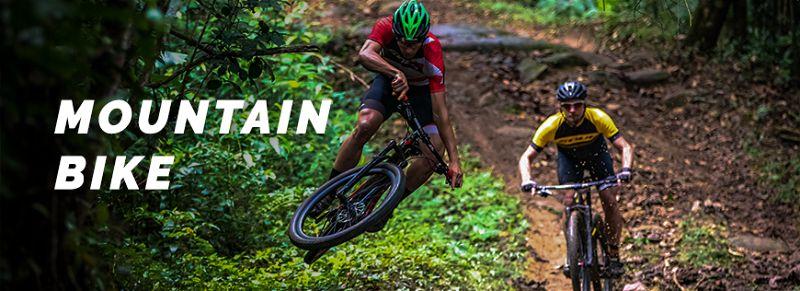 Dois ciclistas fazendo trila com bicicleta em local com diversos obstáculos