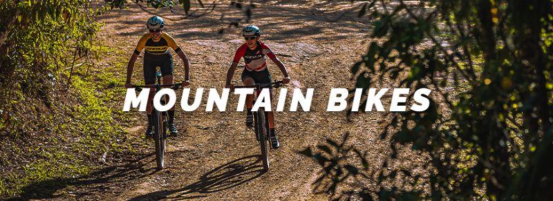 Dois ciclistas andando de mountain bike em estrada de terra