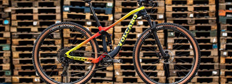 Bicicleta mountain bike com suspensão em frente a paletes empilhados